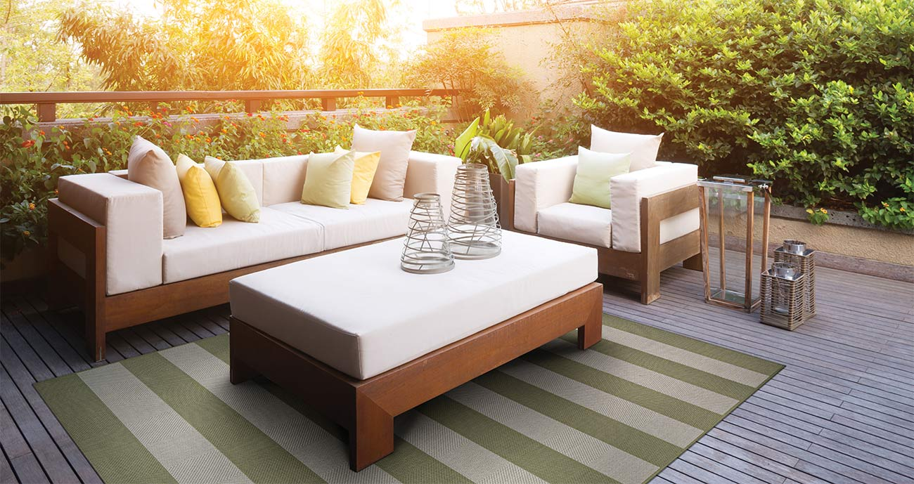 Brown outdoor deck with white couches, sea green and tan area rug, with sunset and bushes in background