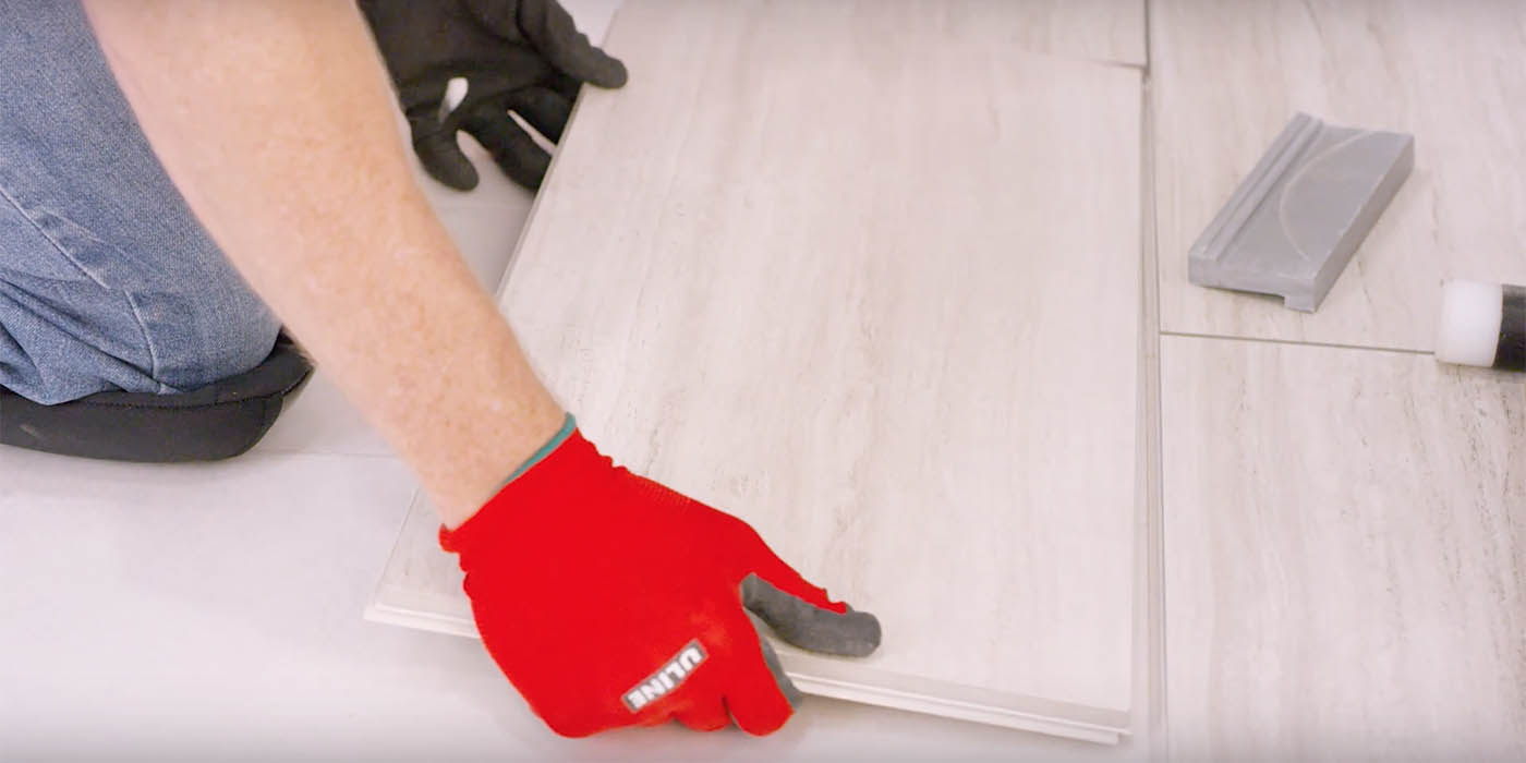 Installer with red gloves installing Daltile's RevoTile white porcelain tile product